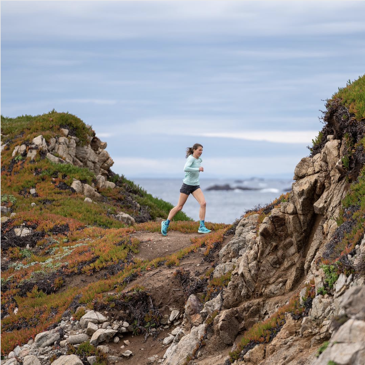 Woman running on a mountain by the ocean wearing a blue sweatshirt, dark shorts and bright blue running shoes