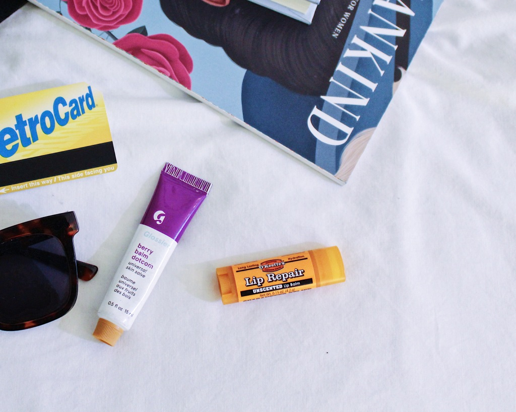 close up of tote bag contents including metro card, sunglasses, Glossier Balm Dotcom, and O'Keefe's Lip Repair