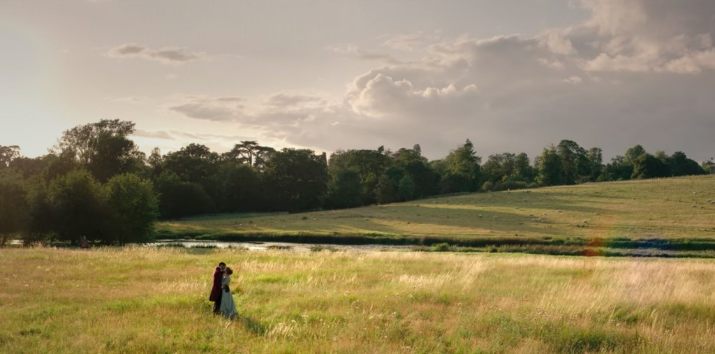 Screen still from Netflix's Bridgerton series with a man in a dark red coat kissing a woman in a light blue dress in a field of grass with trees and clouds in the distance